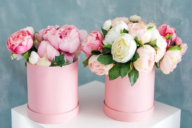 Цветы в круглых роскошных подарочных коробках. букет из розовых и белых пионов в бумажной коробке. макет шляпной коробки цветов с бесплатным copyspace для текста. оформление интерьера в пастельных тонах.