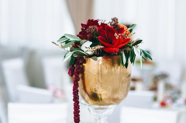 Цветы в небольших винтажных вазах золотистого цвета на свадебном столе. ресторан перед свадьбой.