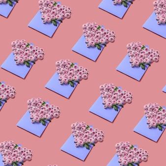 パステルカラーの背景に手作りの封筒にハートの形をした花。クリエイティブな挨拶パターン。