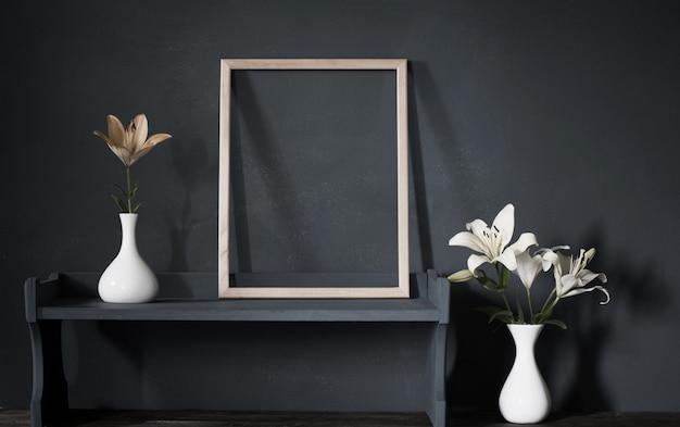 Цветы в вазе и деревянной раме на фоне темной стены