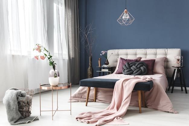 파스텔 침실에 회색 모피가 있는 디자인 바구니 옆에 있는 작은 테이블의 꽃병