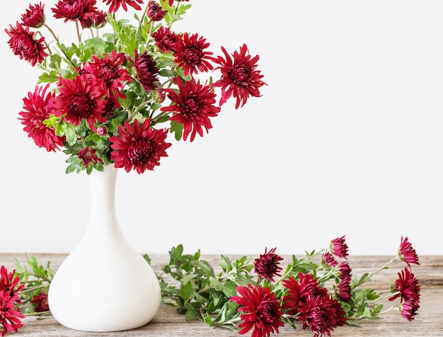 Цветы в вазе на деревянном фоне