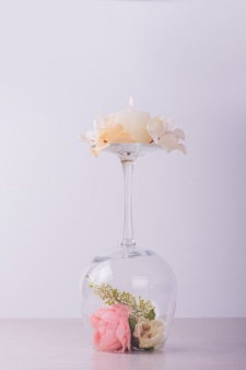 Flowers inside wine glass and candle.