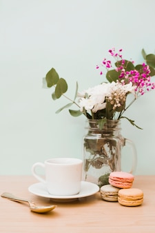 Flowers in jar with cup; spoon and macaroons on wooden desk against wall
