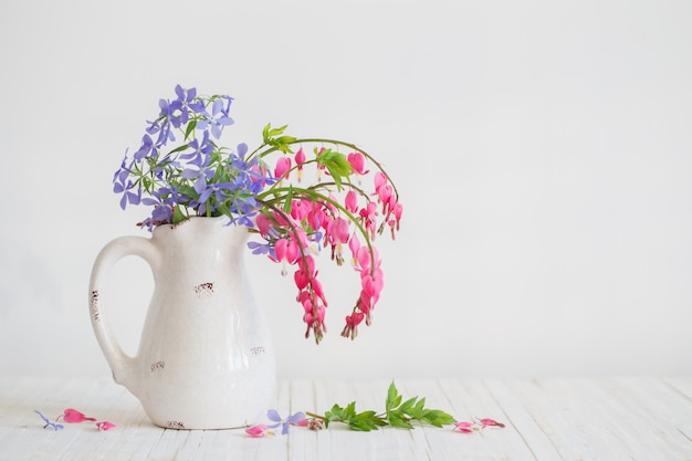 Flowers in jug on white