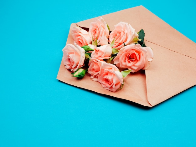 Flowers in a kraft envelope, copy space, blue background