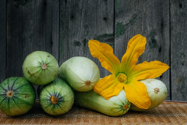 Flowers, leaves and fruits of zucchini isolated on a wooden background.