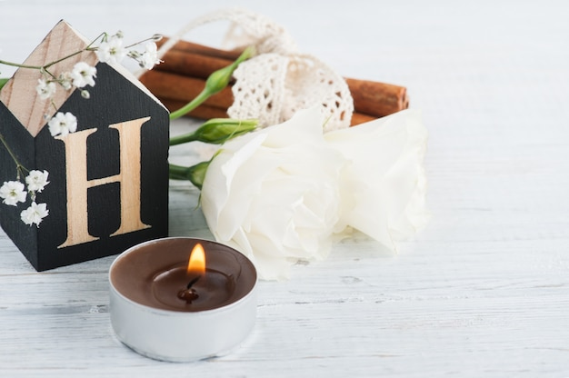 Flowers and lit candle, wooden letter h