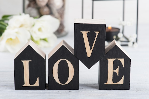 Flowers and lit candle, wooden letter love