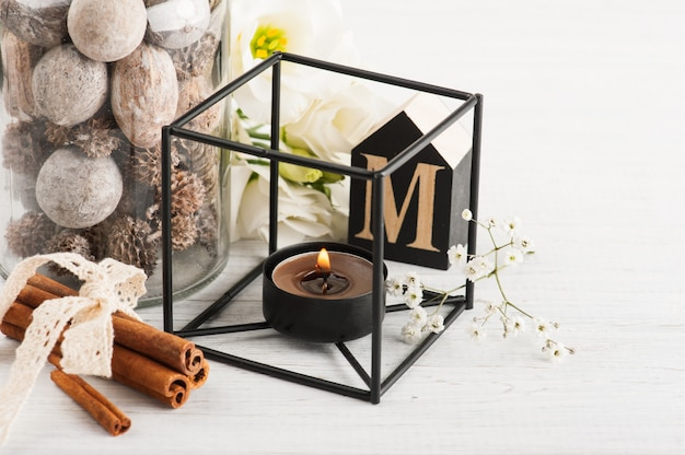 Flowers and lit candle, wooden letter m