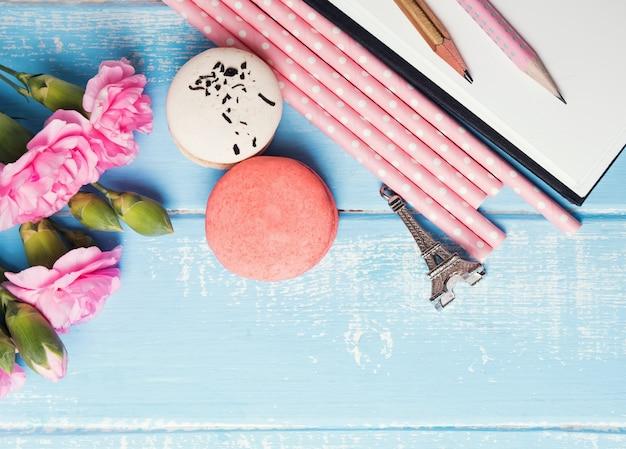 花、マカロン、紙ストロー、鉛筆、青いテーブルの上のお土産エッフェル塔、上面図