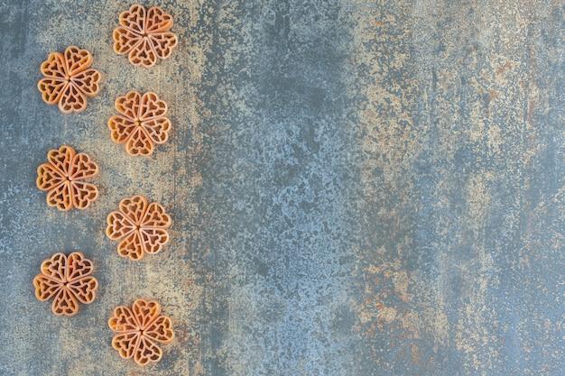 대리석 배경에 마카로니로 만든 꽃.