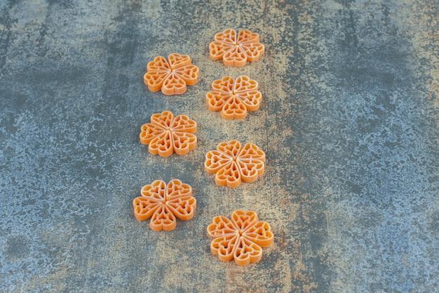 Цветы из макарон на мраморной поверхности.