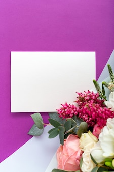 Flowers mock up gift card. congratulations card in bouquet of roses, tulips, eucalyptus on purple background.