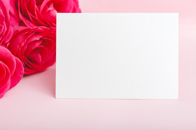 Flowers mockup congratulation. wedding invitation card in bouquet of pink red roses on pink background.
