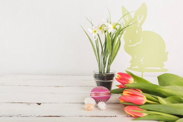 Flowers near easter eggs and bunny
