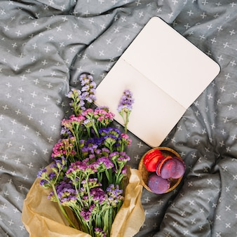 Flowers near macaroons and notebook on bed