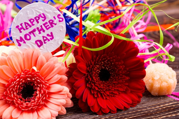 Flowers near mother's day card. candy and colorful streamer. bright gift for mommy. attention and grattitute on holiday.