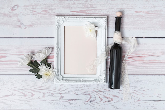 Flowers near photo frame with paper and bottle