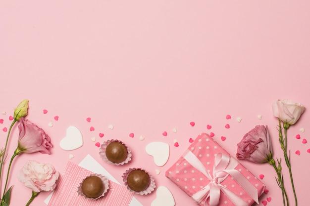 Цветы возле открытки на подарочной коробке и шоколадные конфеты