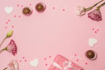 Цветы возле подарочной коробки и шоколадные конфеты