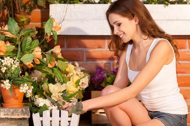 Цветам нужно нежное прикосновение. привлекательная молодая женщина регулирует цветы в горшке и улыбается