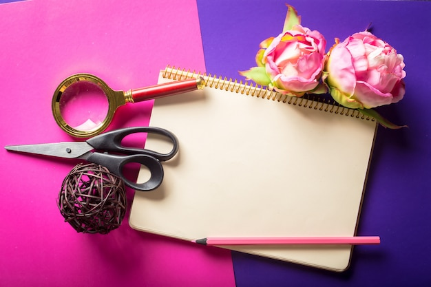 Flowers and a notebook composition with scissors and a magnifying glass