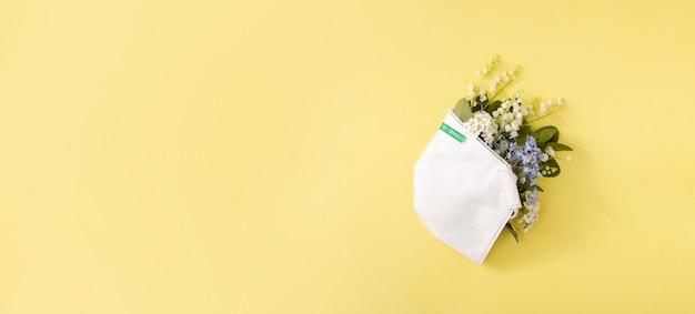 노란색 배경에 복사 공간이 있는 의료용 마스크에 은방울꽃과 물망초 꽃. 계절 독감 및 알레르기의 창의적인 배너