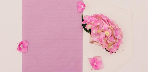 デザイン用のコピースペースのある封筒にピンクのアジサイの花。
