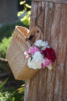 Цветы розовых красных и белых пионов в плетеной корзине на деревянном столе на деревянном фоне