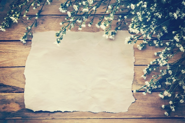 Flowers and old paper on wood texture background with copyspace. vintage style.