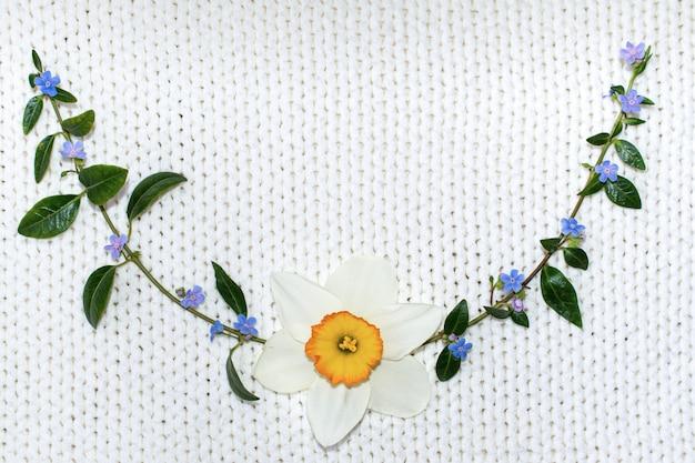 니트 직물의 흰색 배경에 꽃입니다.