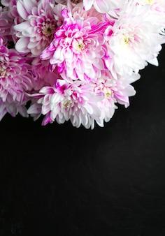 검은 배경에 꽃입니다. 국화 꽃다발. 꽃잎이 있는 완벽한 플랫 레이. 해피 어머니의 휴일 엽서입니다. 국제 여성의 날 인사말. 광고에 대한 생일 아이디어. 공간 장소를 복사합니다.
