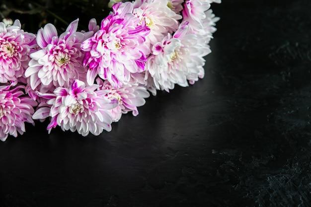 검은 배경에 꽃입니다. 국화 꽃다발입니다. 꽃잎이 있는 완벽한 플랫 레이. 해피 어머니의 휴일 엽서입니다. 국제 여성의 날 인사말. 광고에 대한 생일 아이디어. 공간 장소를 복사합니다.