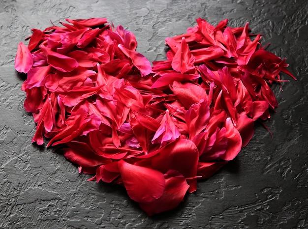 黒の背景に花。牡丹の花びらからの心。バレンタインデーの挨拶。広告や招待のアイデア。