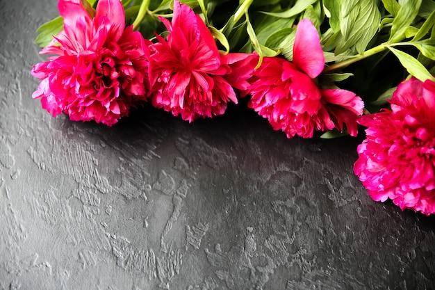 검은 배경에 꽃입니다. 모란 꽃다발. 꽃잎이 있는 완벽한 플랫 레이. 해피 어머니의 휴일 엽서입니다. 국제 여성의 날 인사말. 광고에 대한 생일 아이디어. 초대.