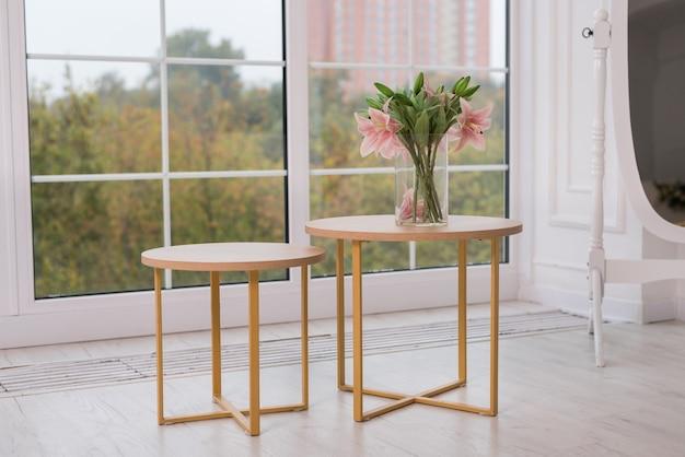 木製のコーヒーテーブルとぼやけた窓の背景に花。