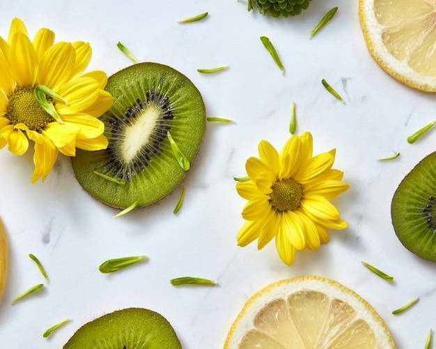 花は黄色、緑の花、キウイとレモンのスライスからパターン化されます。有機成分からフラットレイ春の花の背景。