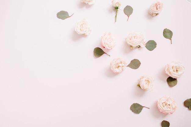 Цветочный узор из бежевых роз, веток эвкалипта на бледно-пастельно-розовом