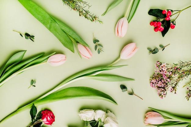 緑の背景にピンクのチューリップ、バラ、オトギリソウの花で作られた花のパターン。平置き