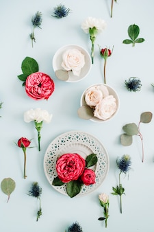 Flowers pattern made of red and beige roses on plate, white carnation and eucalyptus branches on pale pastel blue