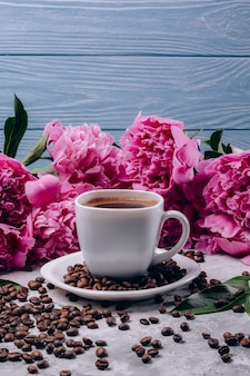 Flowers of peonies with pink buds and coffee in a cup