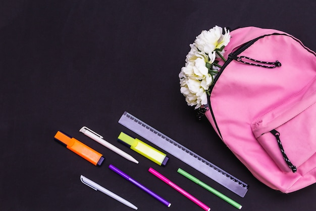 Flowers in a pink backpack, scissors, markers, pens on a black background