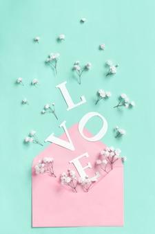 Цветы, розовый конверт и слово любовь на светло-зеленом фоне вид сверху