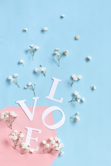 Flowers, pink envelope and word love on a light blue background top view