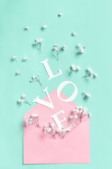 Flowers, pink envelope and word love on a light green background top view