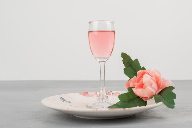 꽃, 접시 및 회색 표면에 장미 와인 한 잔.