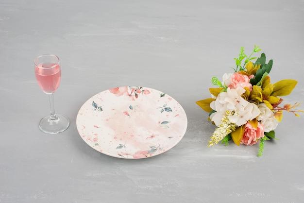 Fiori, piatto e un bicchiere di vino rosato sulla superficie grigia.
