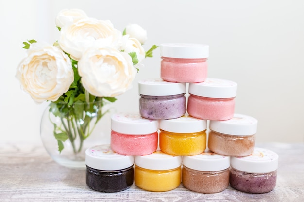 Flowers and a pyrmid of body scrub jars of different colors