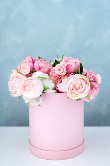 Flowers in round luxury present box. bouquet of pink and white peonies in paper box. mock-up of hat box of flowers with free copyspace for text. interior decoration in in pastel colors.